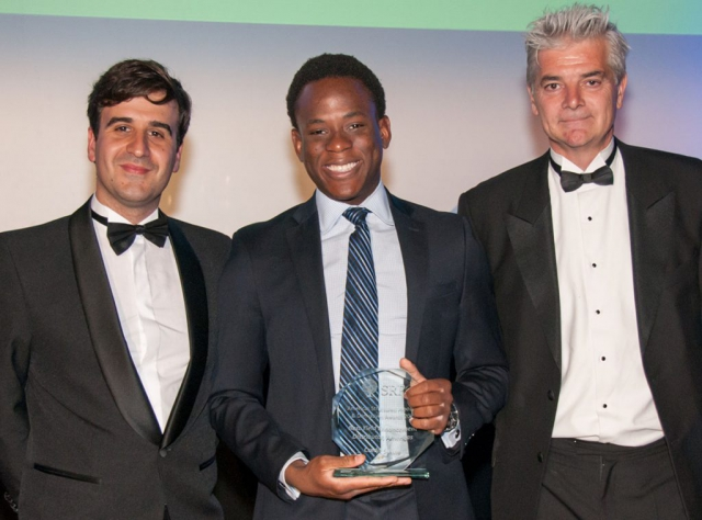 young man smiles and holds the award he just received