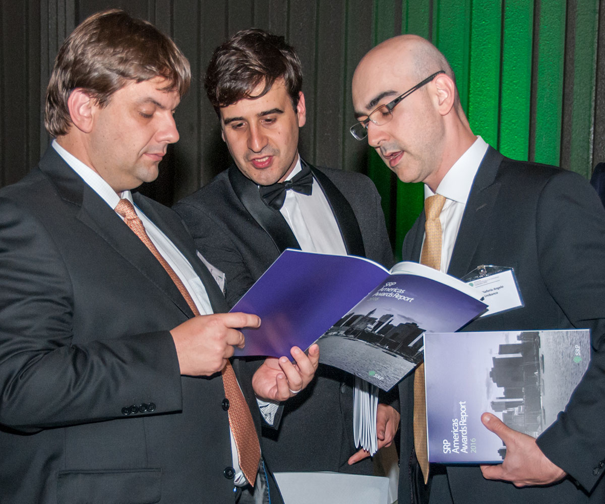 three men examine the program at an awards event