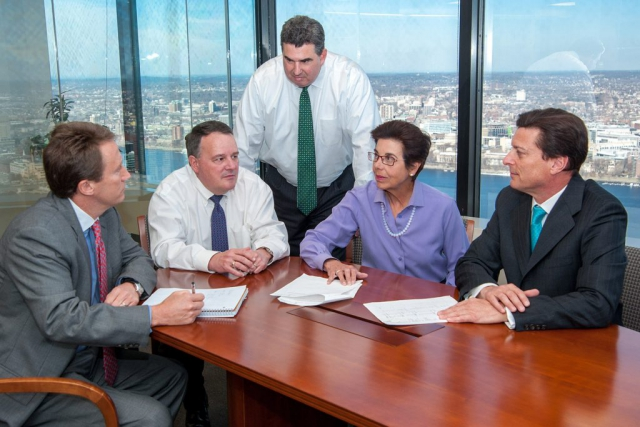 five executives meet in a conference room with an expansive view of the city